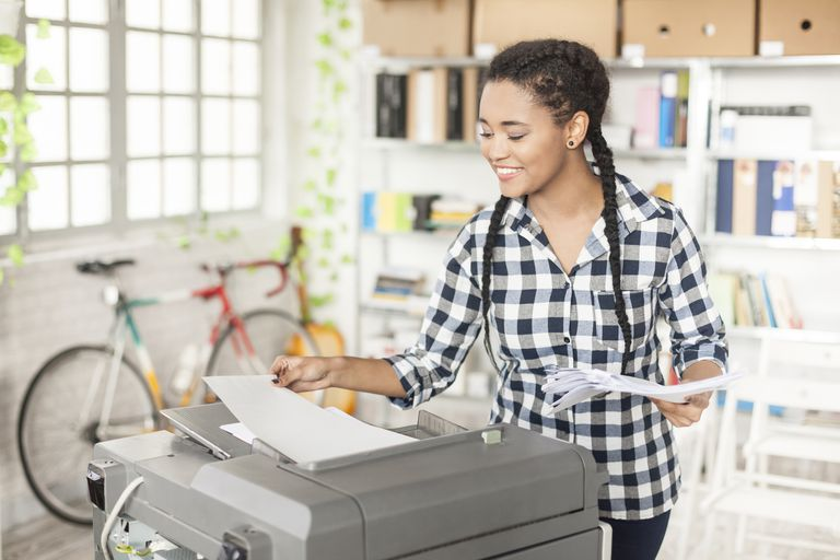 Young female assistant using copy machine at workplace