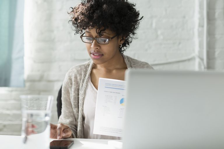 Woman working on laptop and mobile device with financial reports