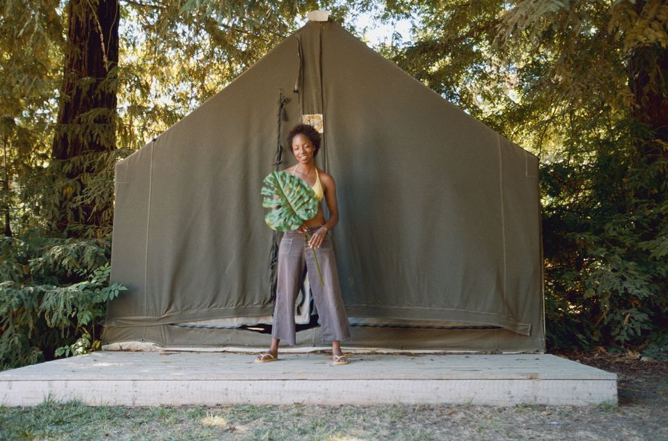 Woman holding leaf outside tent on concrete slab.