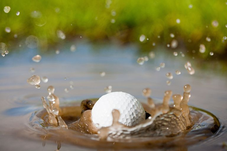 A golf ball splashes into a water hazard