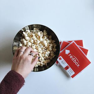 A bowl of popcorn and Redbox movies.