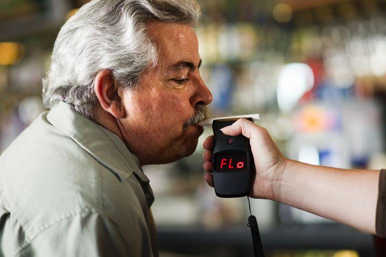 man blowing into breathalyzer test