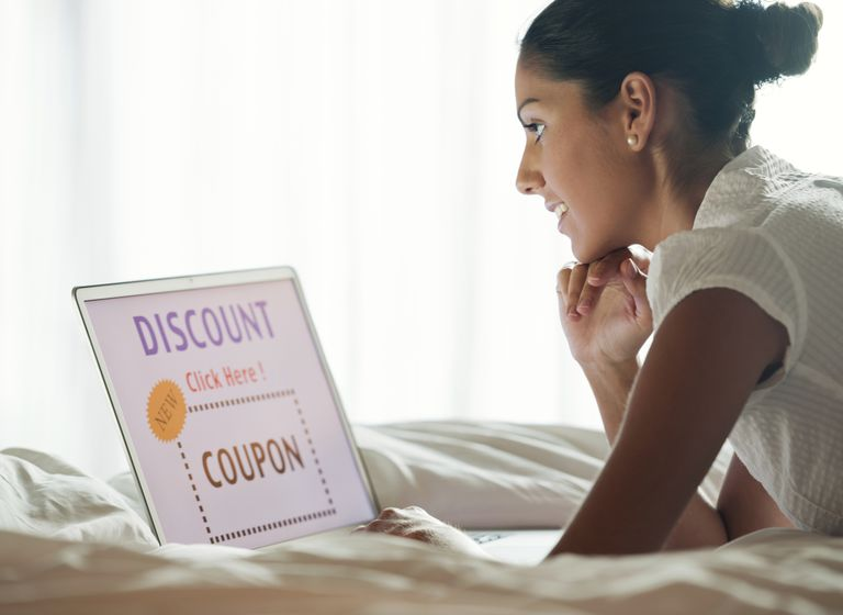 Woman discount shopping on laptop in bed