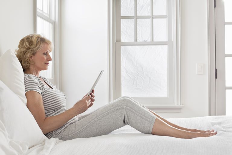 A woman in bed using an ipad.