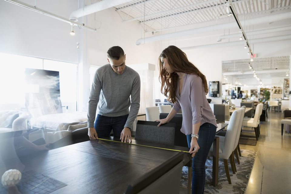 Couple measuring dining table in home furnishings store