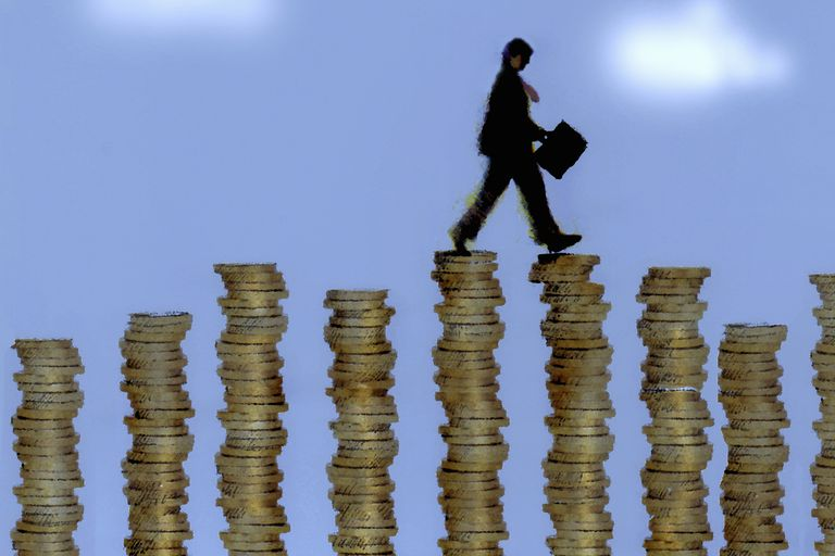 Man walking on tall stacks of coins