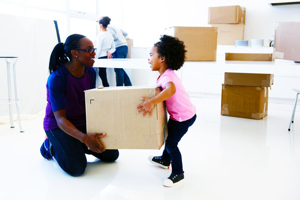 African American mother holding a packed box with her daughter