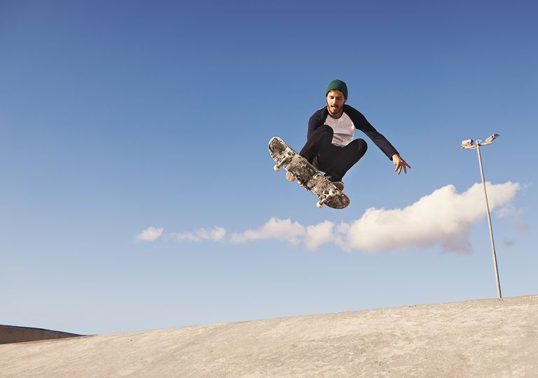 A young man doing tricks on his skateboard at the skate park.