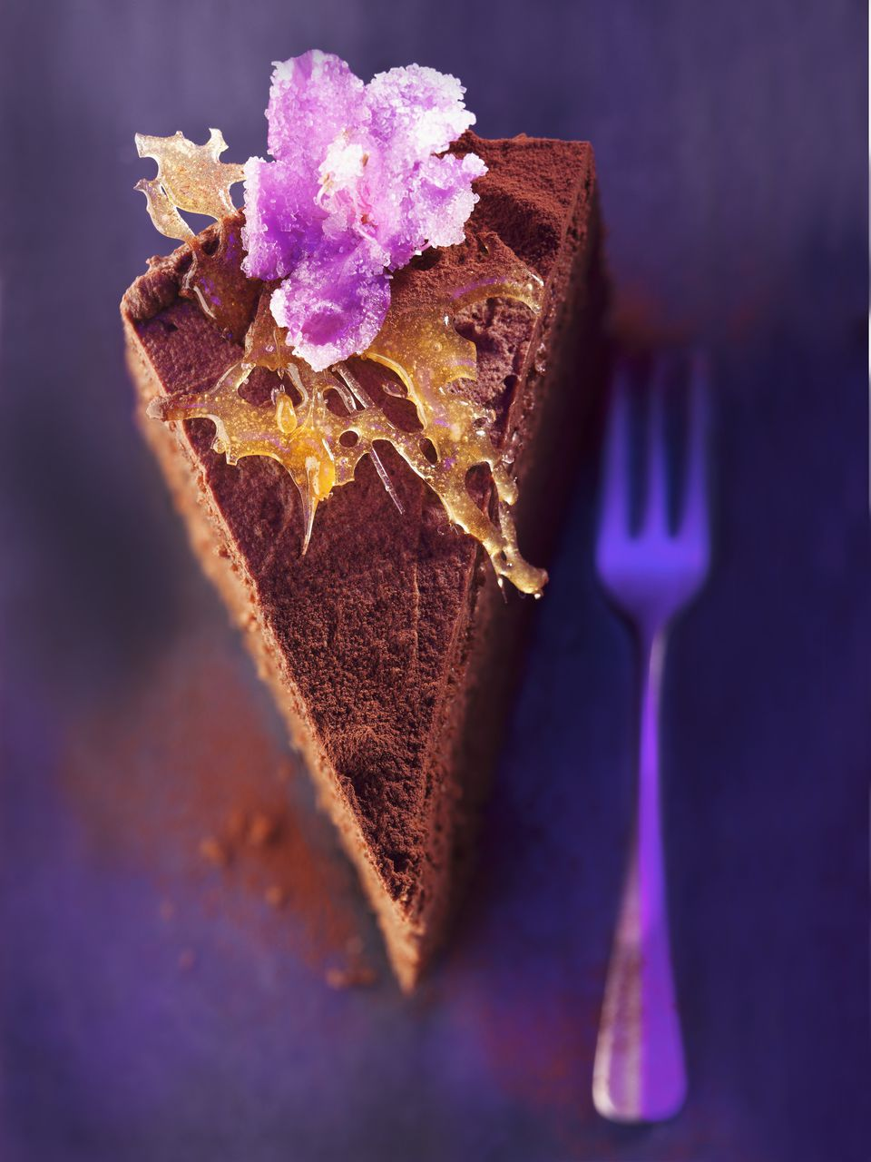 Slice of chocolate layer cake with caramel and candied flowers