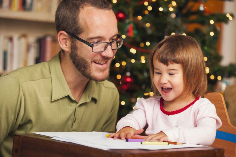 Picture of a father and daughter writing in front of the Christmas tree