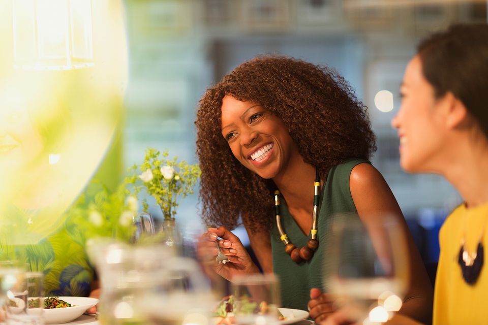 Women friends laughing and dining at restaurant table