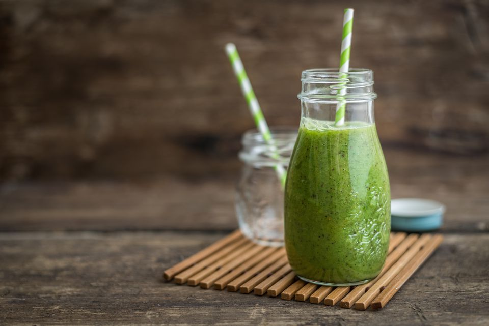 green smoothie in a milk glass with straw