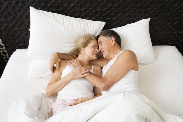 Mature couple embracing in bed, elevated view