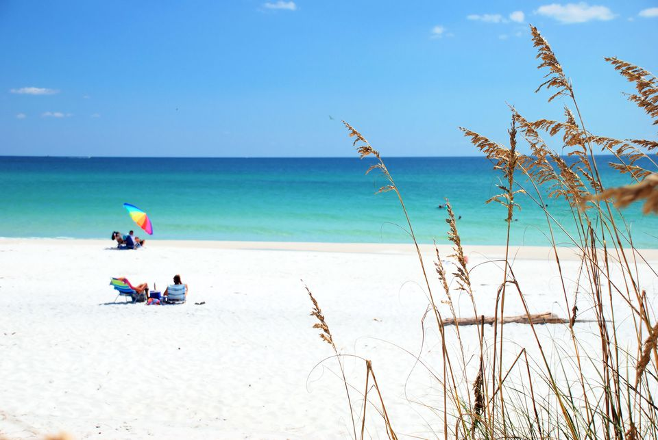Beachgoers enjoying white sand and emerald water of Destin, Florida.