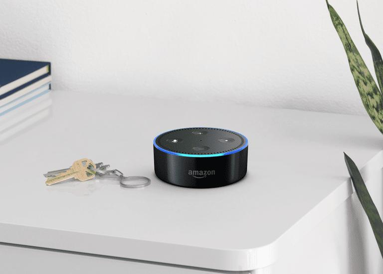 An Amazon Echo dot sitting on a shelf.