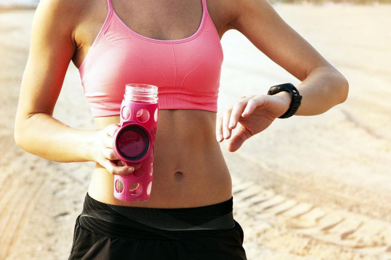 Woman In Workout Gear Looking At Watch