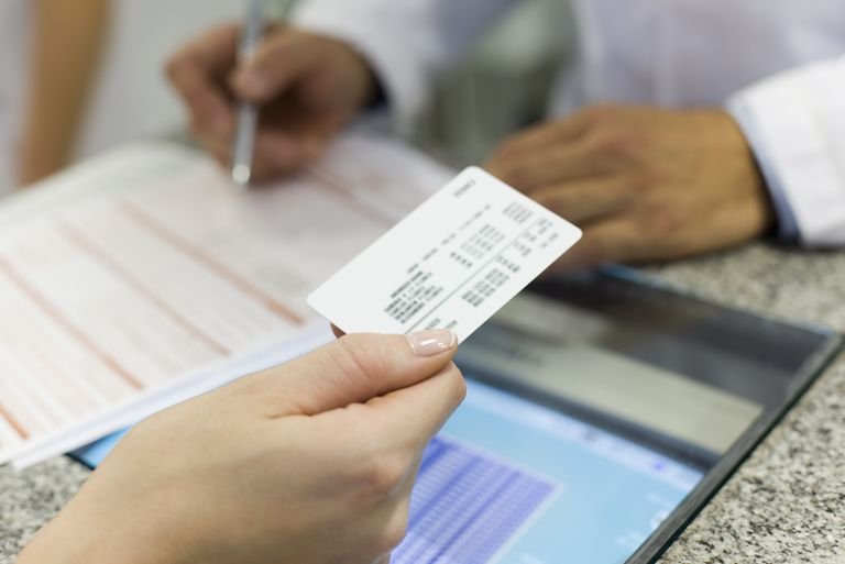 patient handing over insurance card