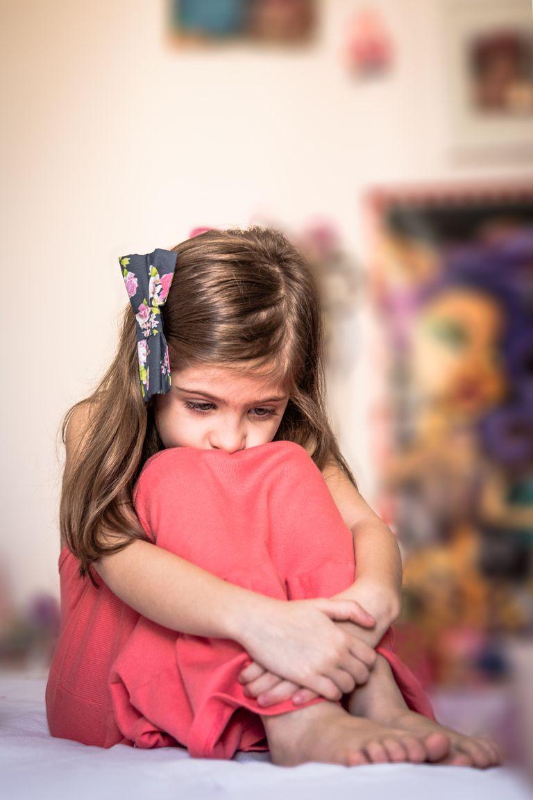 Sad girl hugging knees