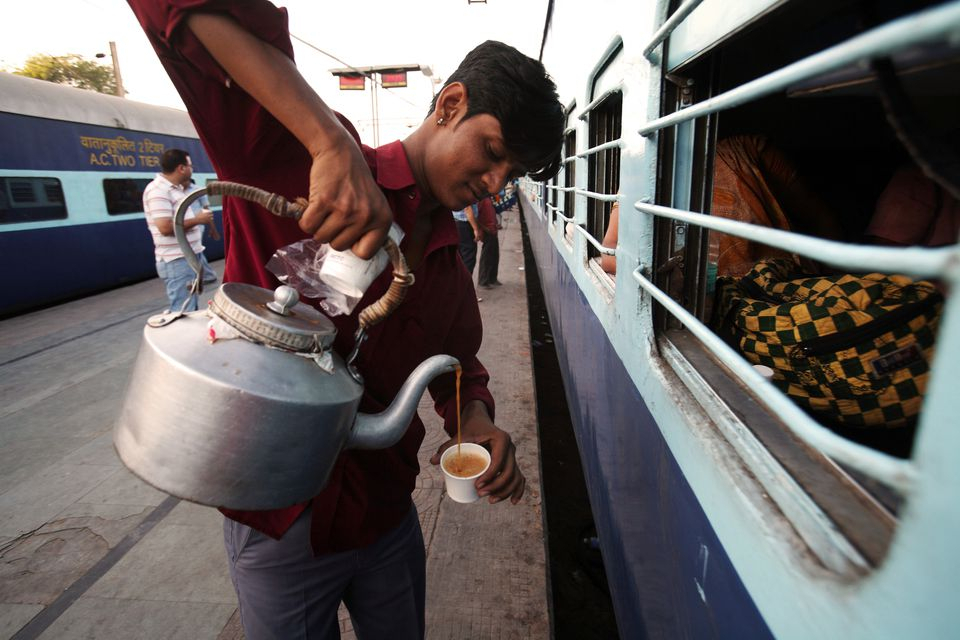 Indian railway vendor selling tea to passengers in train at railway station, India