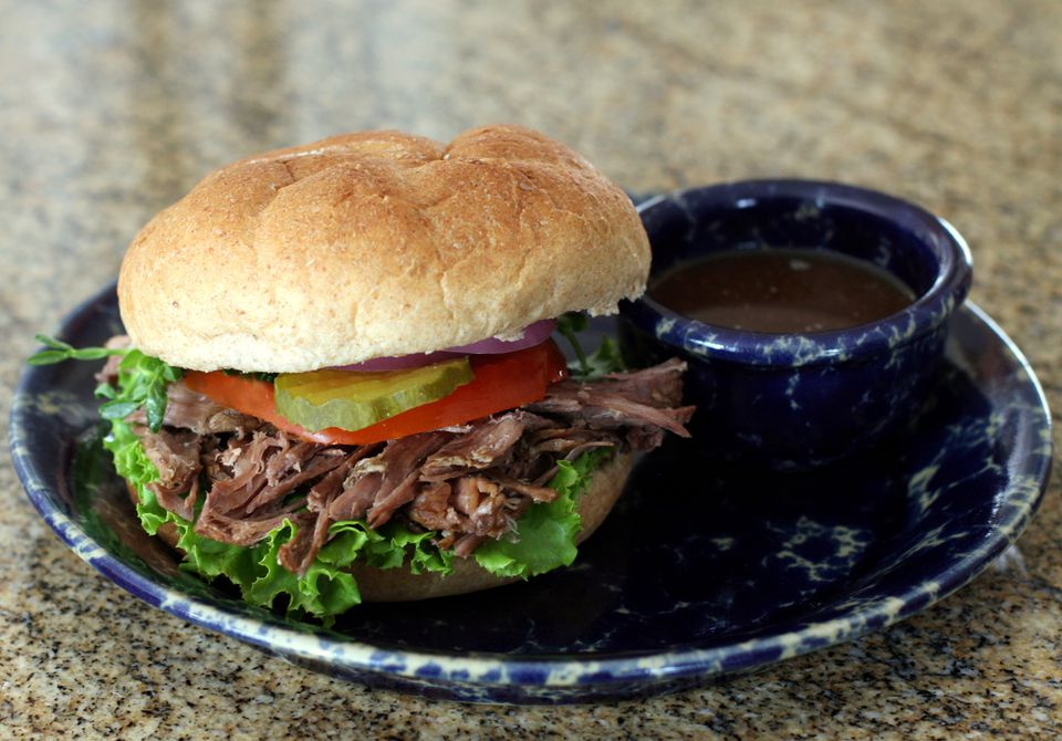 A plate of crockpot Italian beef with dipping sauce