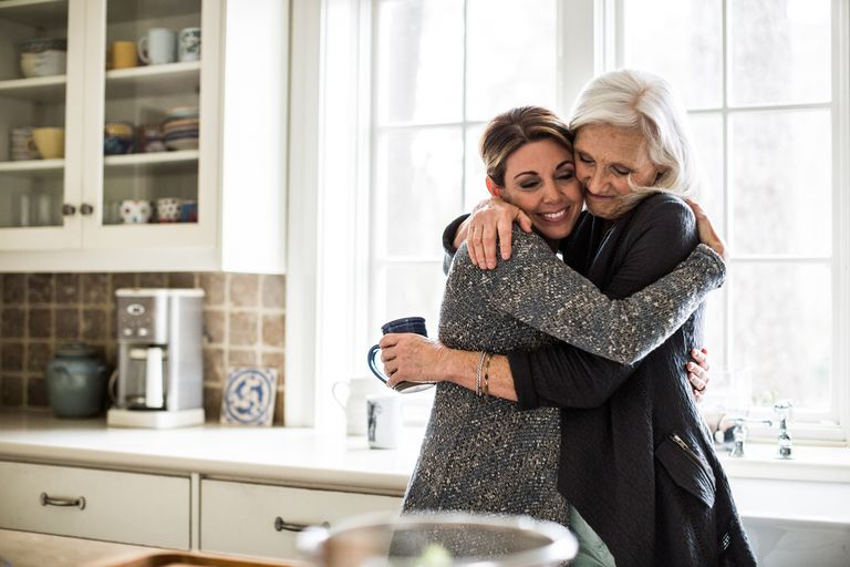 Woman hugging her mother in the kitchen