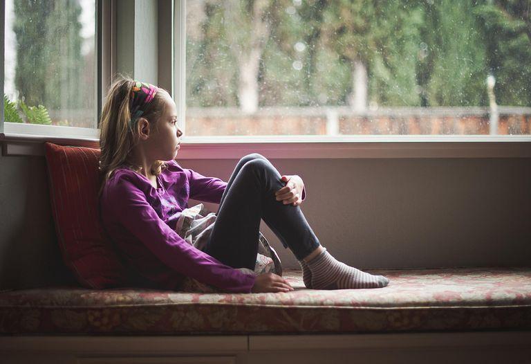 Sad young girl looking out window