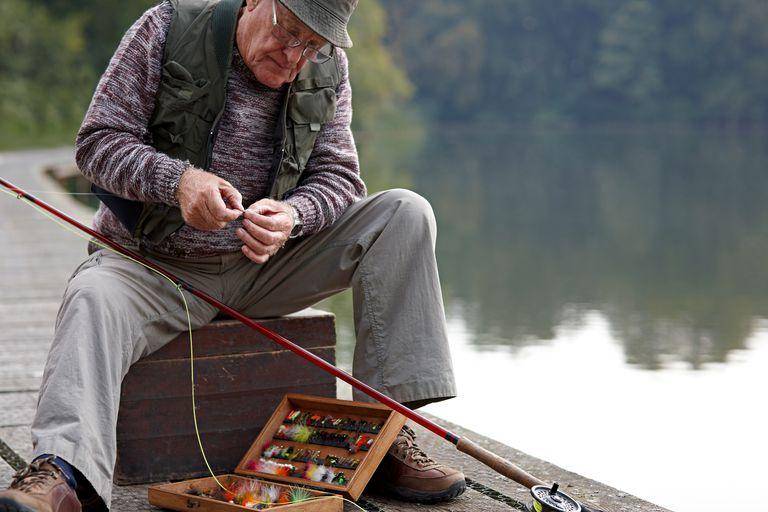 Elderly man on a dock tying a fly onto a fishing pole
