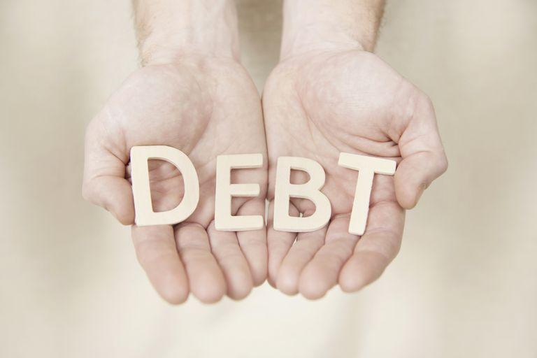 Hands holding debt letters