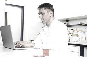 man writing on laptop in lab