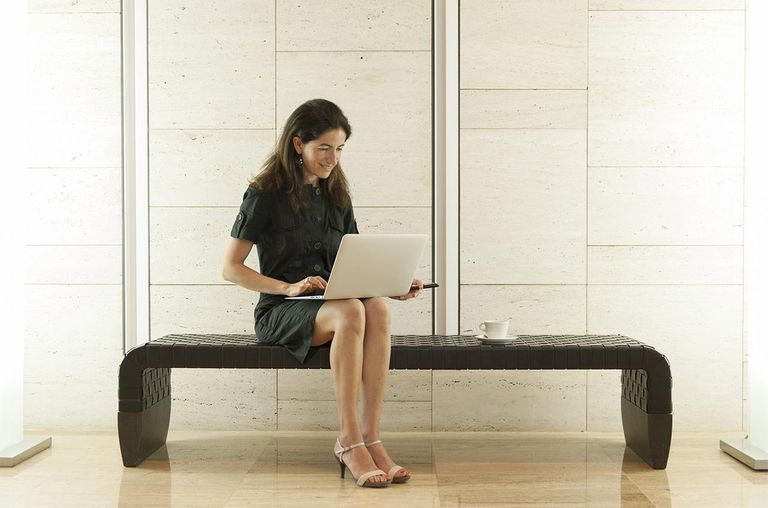 Woman using laptop computer in lobby