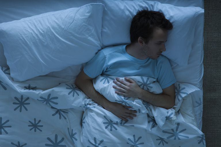Man awake in bed under sheets
