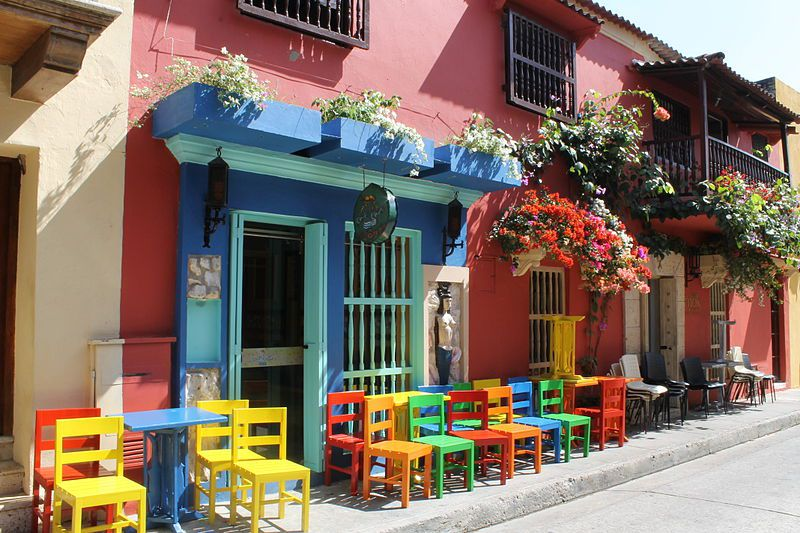 Colorful chairs in front of a blue and pink wall with flowers in Cartagena, Colombia.