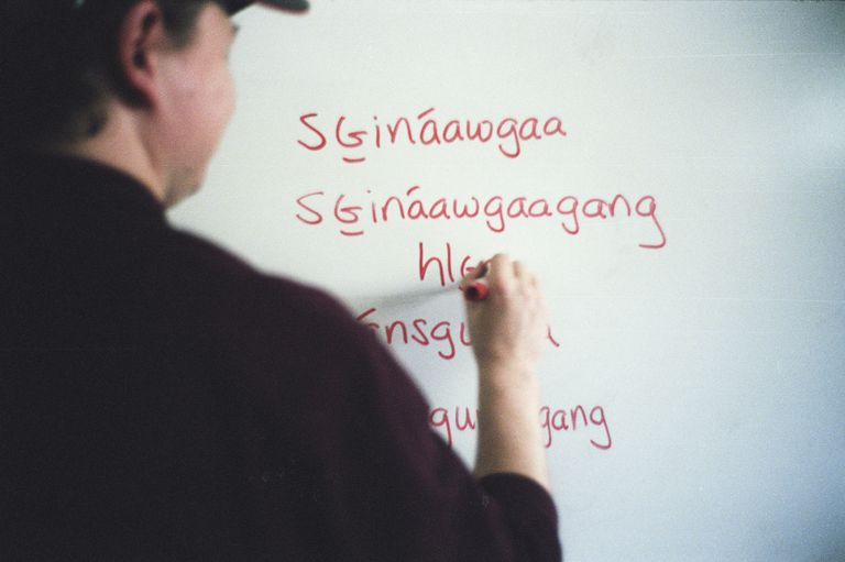 Picture of a man writing Haida words on a marker board