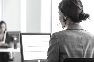 Businesswoman talking on headset at desk