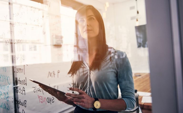 Shot of woman reading notes on a glass wall in an office