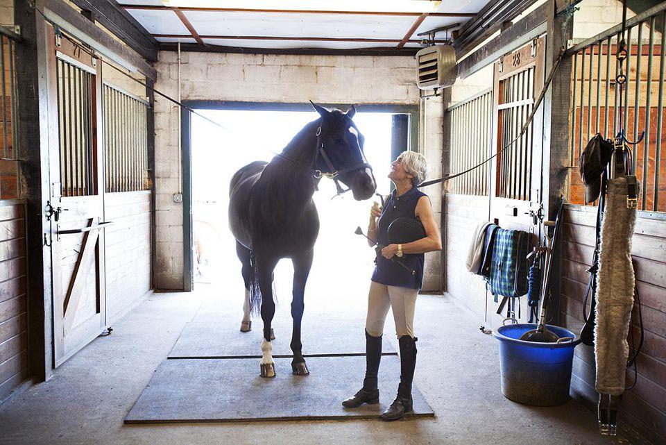 Mature Female Equestrian Tending to her Horse