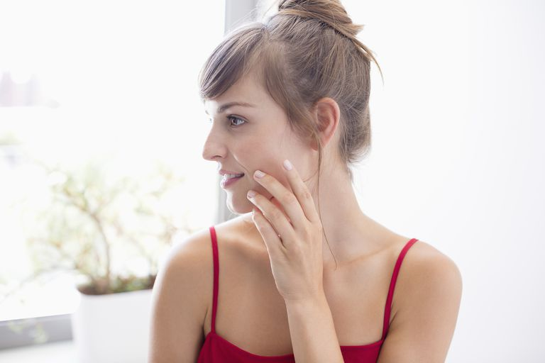 Woman applying beauty products to face