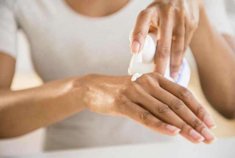 Close up of woman's hands applying moisturizer