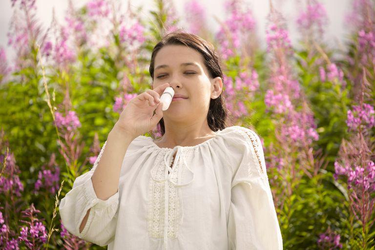 Nasalcort vs. Flonase. Woman using allergy relief nasal spray