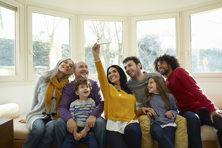 Multi generation family on window seat using smartphone to take selfie