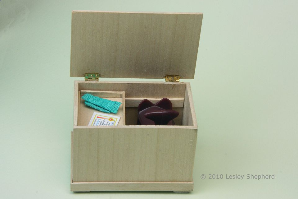 Interior of a dolls house scale wooden tack trunk with moveable drawers and space for a scale saddle