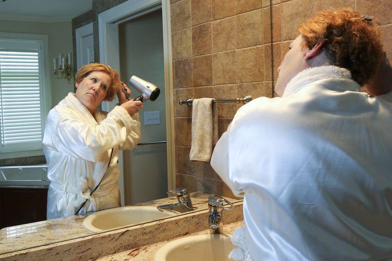 Woman drying hair standing at bathroom vanity