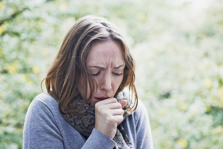 Woman coughing outdoors