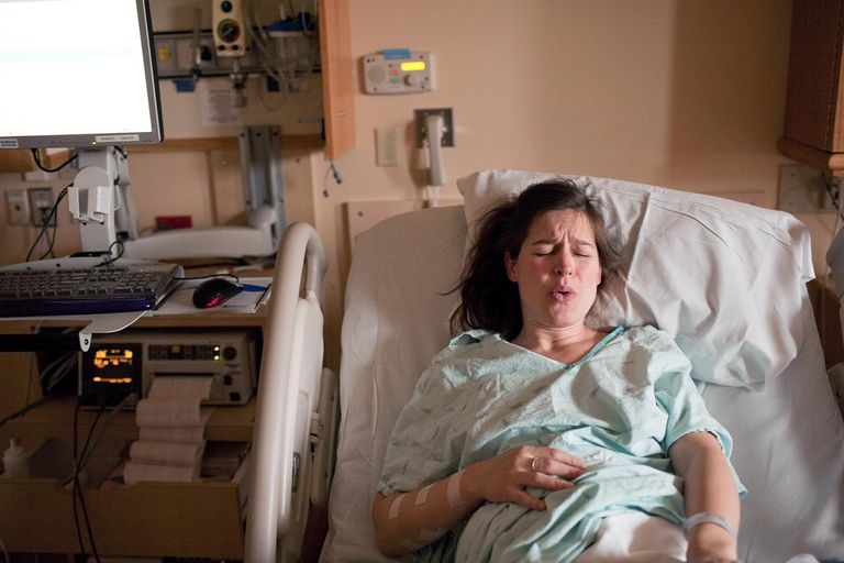 Pregnant woman in labor on hospital bed