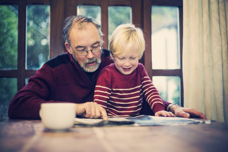 A grandfather reading something with his grandchild