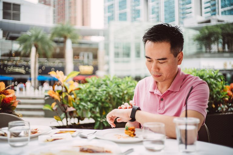 Man looking at watch while eating outside