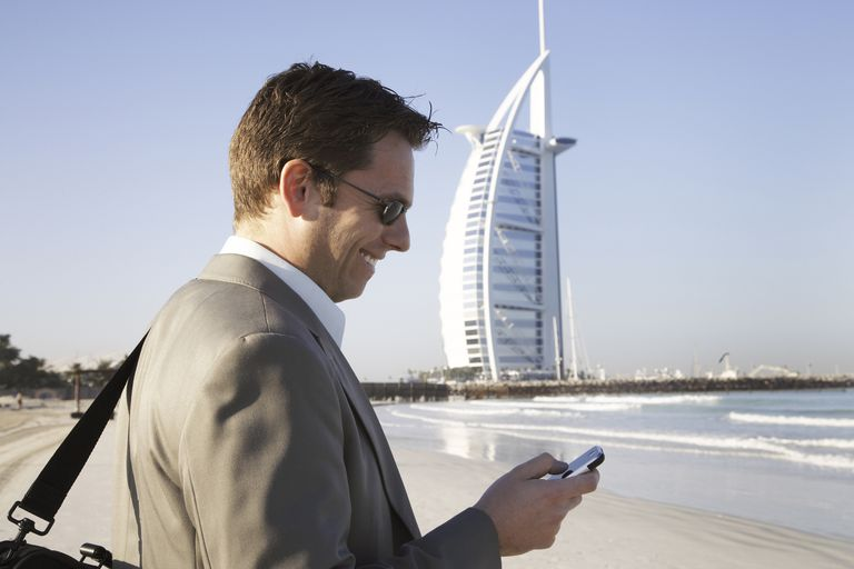 Caucasian businessman using cell phone on beach, Dubai, United Arab Emirates