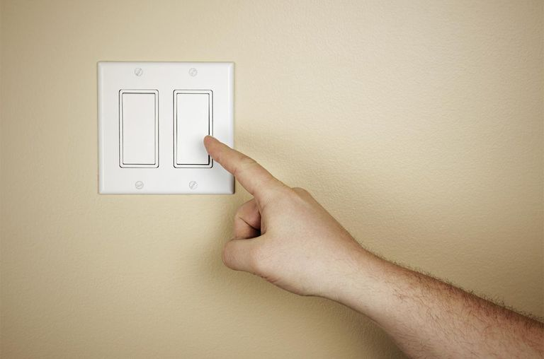 A male hand moves to turn off a light switch