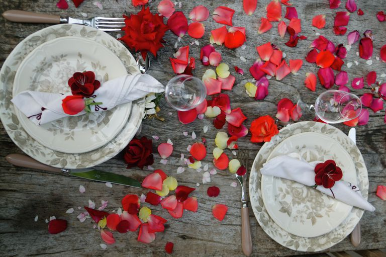Dinner setting for two with rose petals