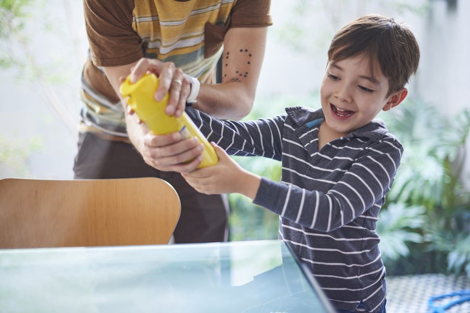 Hispanic boy helping father spray cleaner on table